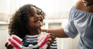 A little girl holding a smile model for family dentistry education