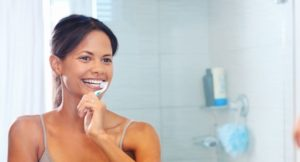 A women following our tips on how to prevent cavities by brushing teeth